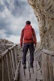 有一个背包的人在一个老木桥的一次远足期间 图库摄影