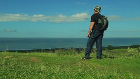 有一个背包的人在他的后站立在山边缘并且敬佩湖的看法 ?? 股票录像