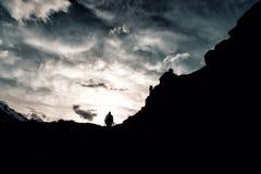 有一个背包的剪影人在伪装在山的上面起来 库存图片