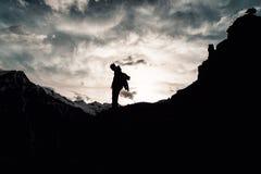 有一个背包的剪影人在伪装在山的上面起来 免版税库存照片
