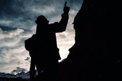 有一个背包的剪影人在伪装在山的上面起来 库存照片