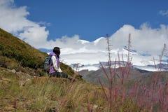 有一个背包的女孩在多雪的山背景  免版税库存图片