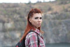 有一个背包的女孩在岩石背景  免版税库存照片