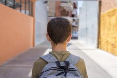 有一个背包的少年男生在他的后面走到学校的 免版税库存图片