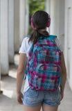 有一个背包的少年学校女孩在她和耳机 库存图片