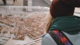 有一个背包的年轻女性游人在她的肩膀审查城市的微型设施有房子的和 股票录像