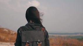有一个背包的年轻徒步旅行者女孩在日落的顶面山 o 影视素材