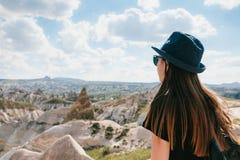 有一个背包的年轻美丽的旅行女孩在小山顶部在卡帕多细亚,土耳其 旅行,成功,自由 图库摄影