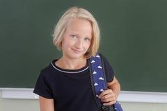 有一个背包的愉快的女小学生青春期前在黑板附近的一间教室 回到学校 免版税库存图片