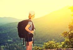 有一个背包的愉快的妇女游人在自然 免版税库存照片