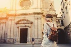 有一个背包的时髦妇女旅客在走在不熟悉的街道上的她在夏天冒险期间 免版税库存图片