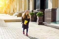 有一个背包的时髦的小女孩在外套和法国贝雷帽跑到学校 免版税库存照片