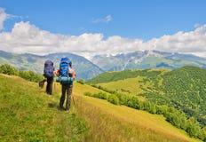 有一个背包的游人在山背景  免版税库存图片