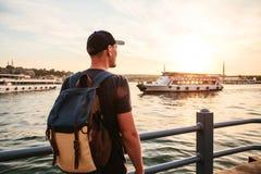 有一个背包的男性游人在Bosphorus旁边的日落在伊斯坦布尔 休闲的概念,远足,假期 免版税库存图片
