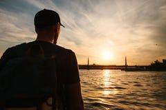 有一个背包的男性游人在Bosphorus旁边的日落在伊斯坦布尔 休闲的概念,远足,假期 库存图片