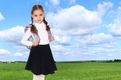 有一个背包的美丽的女小学生在她的肩膀后 免版税库存照片