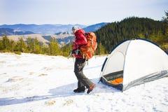 有一个背包的登山人在帐篷附近 免版税库存图片