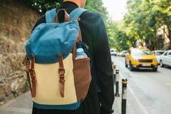 有一个背包的年轻男性游人在大城市等待出租汽车 旅途 观光 旅行 免版税库存照片