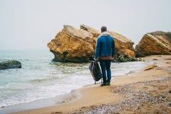 有一个背包身分的旅客在反对美丽的海的一个岩石附近有波浪的,摆在a附近的一个时髦的行家男孩 免版税库存图片