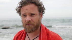 有一个胡子和一个湿头的年轻人以在游泳以后的海为背景与照相机讲话 4?k?? 股票录像