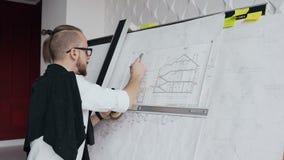 有一个胡子和玻璃一位男性建筑师的特写镜头研究一栋居民住房的项目 股票录像
