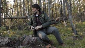 有一个胡子的一个中部年迈的人在树残余部分拍周围的环境的照片与智能手机的,投入 股票录像