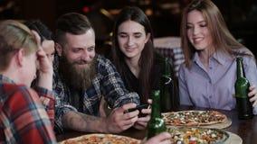 有一个胡子的一个时髦的人在咖啡馆的一张桌上显示他的朋友在电话的照片 股票录像