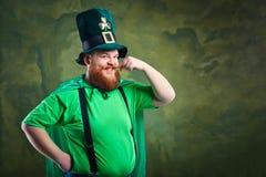 有一个胡子的一个肥胖人在圣帕特里克` s衣服微笑着 免版税库存图片