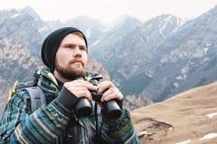 有一个胡子的一个行家人在一个帽子、一件夹克和一个背包在山拿着双筒望远镜,冒险,旅游业 免版税库存图片