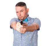 有一个胡子的严肃的成人人在夏天衬衣的一个蓝色蝶形领结有在手拉手瞄准的一个火器的 免版税库存照片