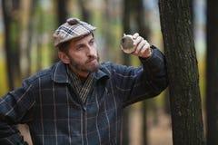 有一个胡子的人在苏格兰盖帽在手中拿着圆的烧瓶 免版税库存照片