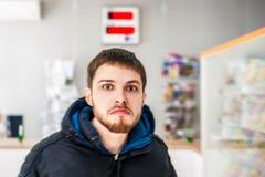 有一个胡子的年轻人与一张哀伤的面孔在背景被弄脏的邮局等待 库存图片