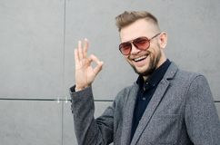 有一个胡子的微笑的人在显示的太阳镜和的夹克好 免版税库存照片