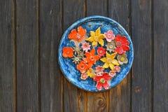 有一个花主题的老陶瓷板材在被风化的木墙壁上 免版税库存照片