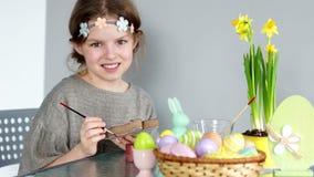 有一个花圈的一个棕色目的女孩在她的头为复活节做准备 孩子看照相机并且快乐地笑 股票录像