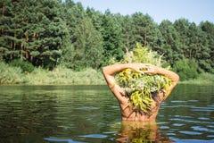 有一个花圈的女孩在她的头在水中 免版税库存照片