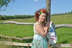 有一个花圈的妇女在顶头和一条五颜六色的围巾在手上在篱芭附近站立 免版税图库摄影