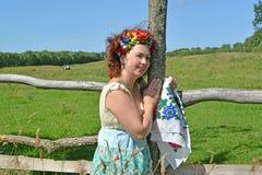 有一个花圈的妇女在顶头和一条五颜六色的围巾在手上笑,站立在篱芭附近 库存照片