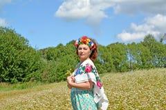 有一个花圈的成熟妇女在顶头和一条五颜六色的围巾 免版税图库摄影
