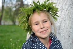 有一个花圈的相当微笑的小女孩在他的头 图库摄影