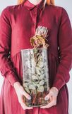 有一个花瓶的女孩在她的有普罗梯亚木的手上 免版税图库摄影