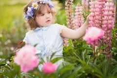 有一个花花圈的愉快的小孩女孩在庭院里 免版税库存图片