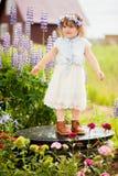 有一个花花圈的愉快的小孩女孩在庭院里 库存照片