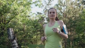 有一个苗条图的一个少妇在森林跑在日落 健康生活方式,做跑的女孩运动员 股票录像