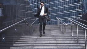 有一个英俊的商人步行沿着向下台阶和电话交谈 库存图片