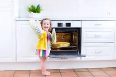有一个苹果饼的可爱的小孩女孩在烤箱 免版税库存图片
