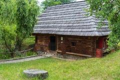 有一个茅屋顶的一个老农村房子位于有一被铺的石导致的绿色草坪它 免版税库存照片