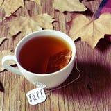 有一个茶包的一个杯子与在它的标签的词秋天 免版税库存照片