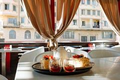 有一个茶壶、杯子和蛋糕的盘子在一个咖啡馆的一张桌上反对窗口 库存照片