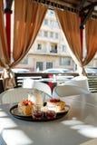 有一个茶壶、杯子和蛋糕的盘子在一个咖啡馆的一张桌上反对窗口 免版税图库摄影